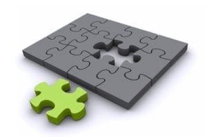 graues puzzle mit einem gruenen puzzleteil ausserhalb