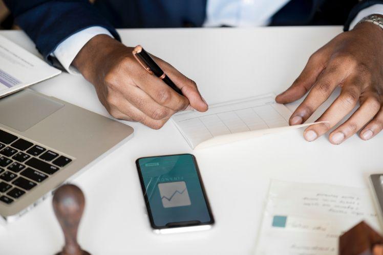 person bei der arbeit mit smartphone notebook und notizen