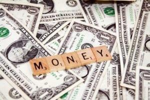 money holzbuchstaben liegen auf geld