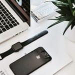 iphone liegt neben armbanduhr und laptop