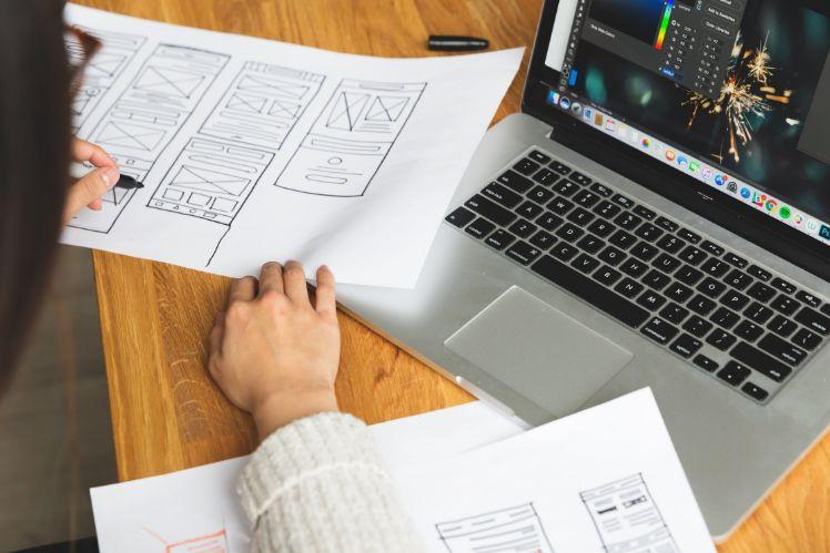 frau erstellt wireframes einer app neben notebook