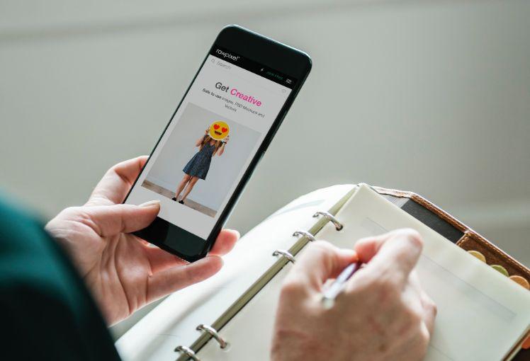 schwarzes smartphone mit get creative app und notizbuch