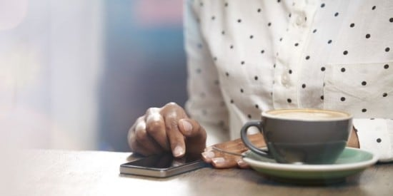 frau mit kaffee bedient smartphone