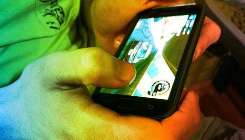 kind spielt mobile game auf smartphone