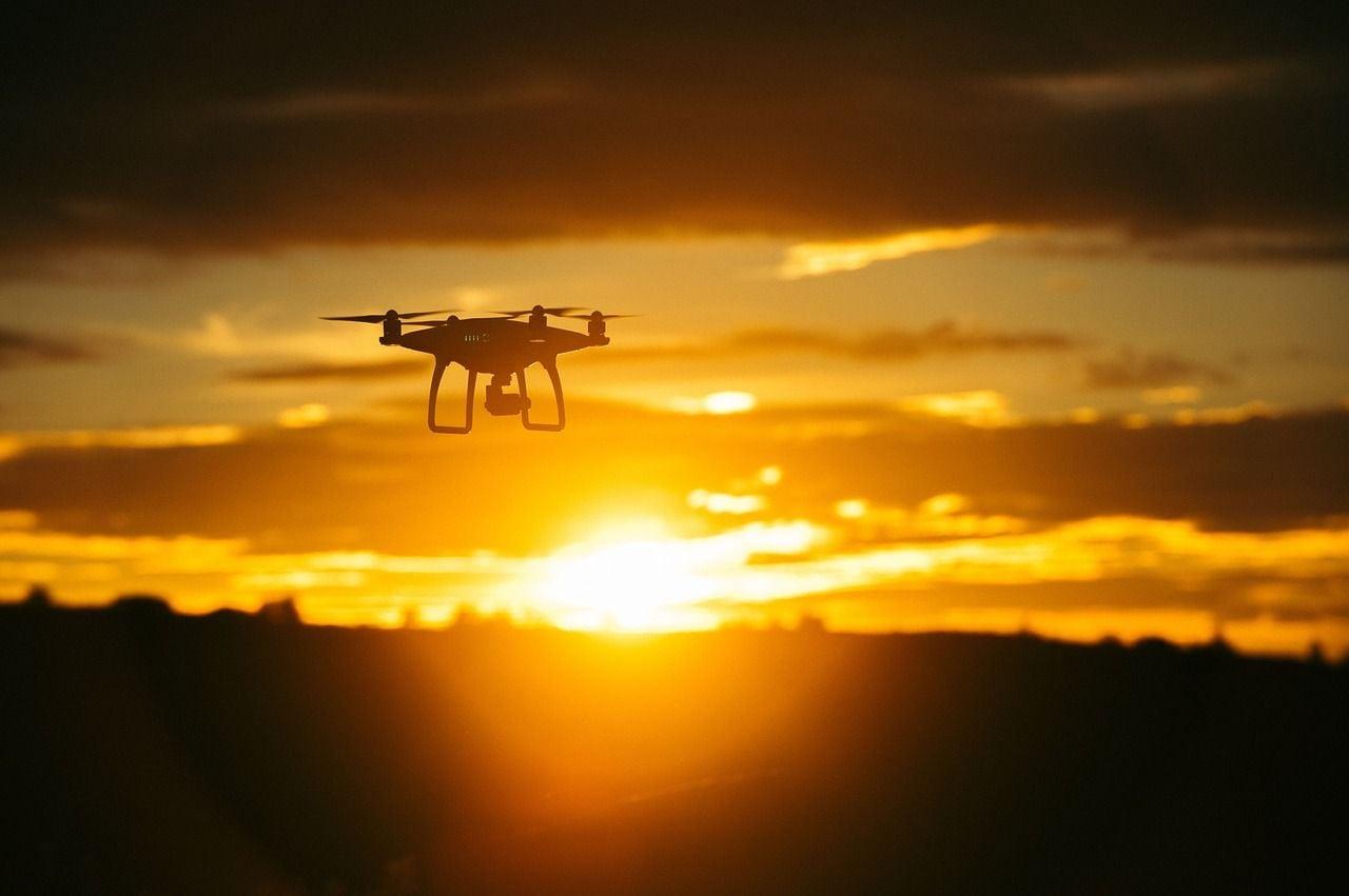 Drohne fliegt bei Sonnenuntergang