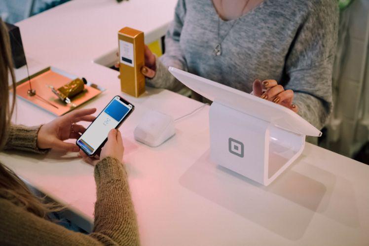 person zahlt mit smartphone an der kasse