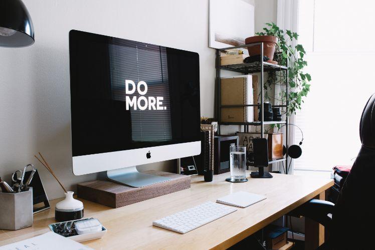 mac bildschirm auf schreibtisch mit aufschrift do more