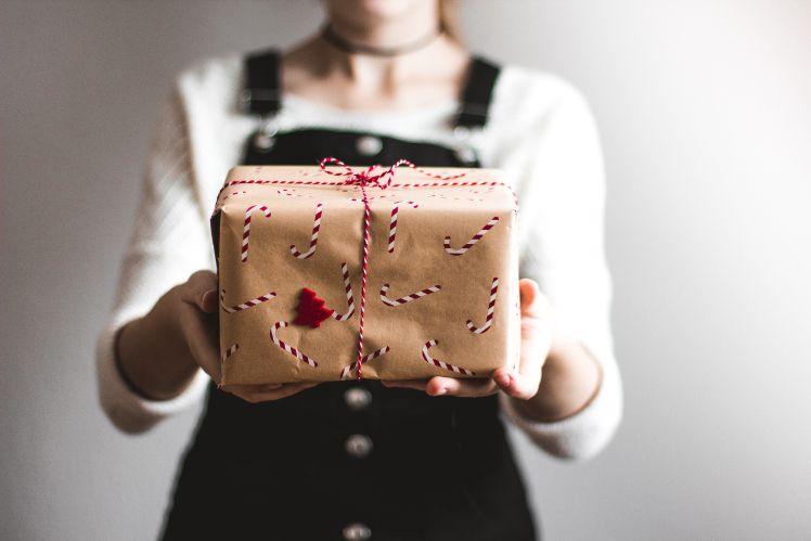 frau haelt weihnachtsgeschenk in der hand