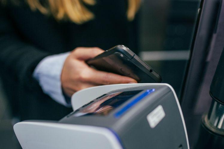 frau haelt smartphone an mobiles bezahlgeraet