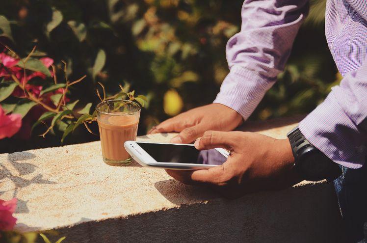 mann im hemd bedient smartphone und kaffee