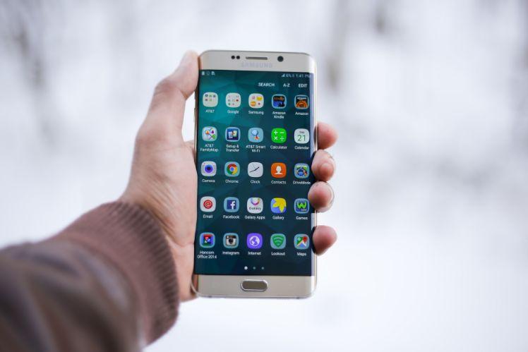 weisses smartphone in hand mit vielen apps