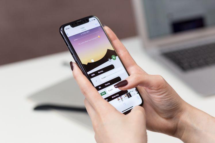Frau haelt schwarzes android phone in der hand