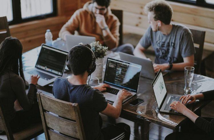 fuenf menschen sitzen an einem tisch mit laptops