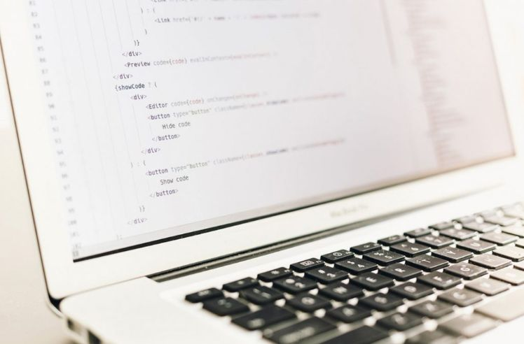 weisses macbook air mit programmiercode auf bildschirm