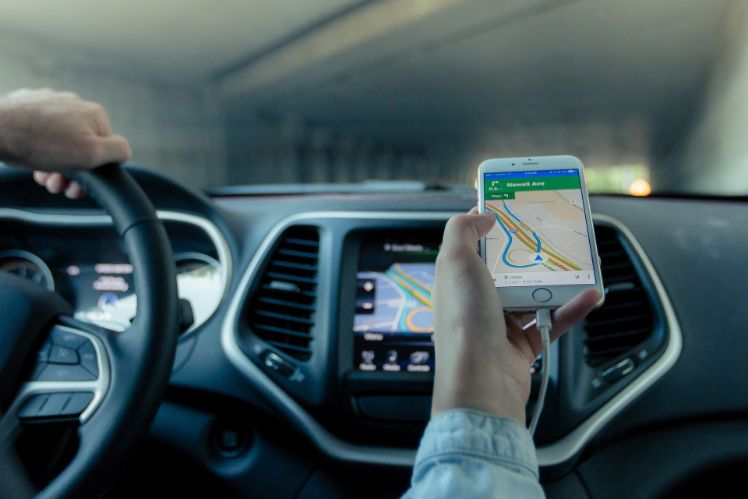 person haelt navigations app in fahrendem auto