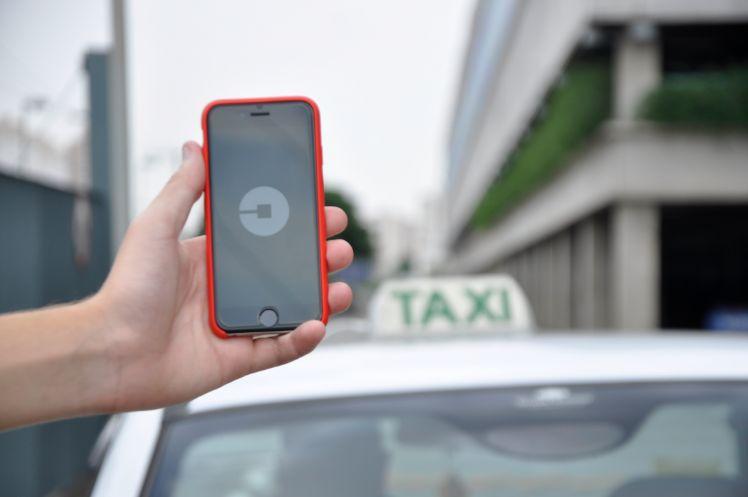 Smartphone mit taxi app wird vor taxi gehalten