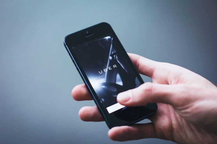 person haelt schwarzes iphone mit uber app
