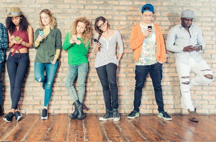 Sechs junge Menschen stehen an der wand mit smartphone in der hand