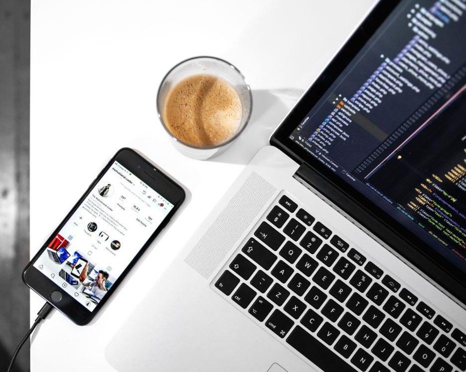 iphone liegt neben kaffee und macbook auf einem tisch