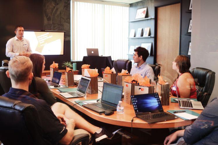 meeting mit vielen personen mit laptops ein mann steht vorne