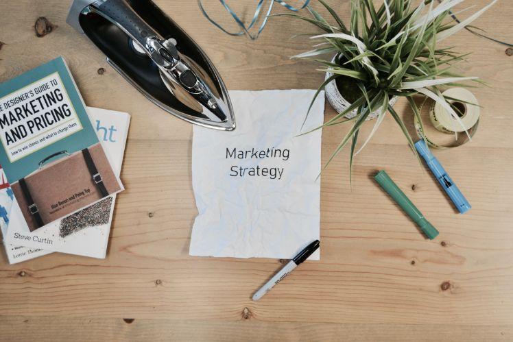 Zettel mit aufschrift marketing strategy neben stiften und buch und buegeleisen