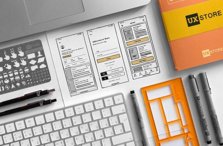 entwurf einer app neben notebook und stiften und buch