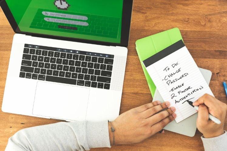 Mann schreibt to do liste neben laptop