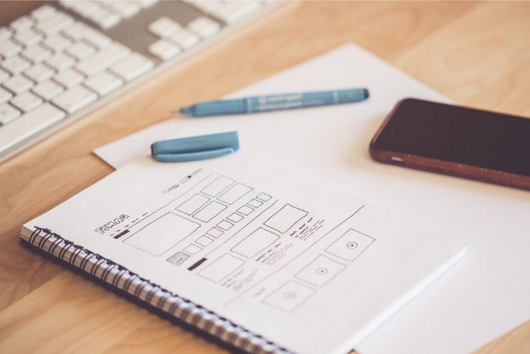 Gezeichneter Entwurf und wireframe einer app auf Notizbuch mit blauem stift
