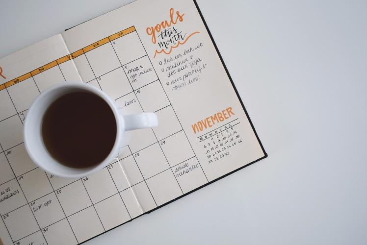 Kaffeetasse steht auf notebook mit Zielplanung