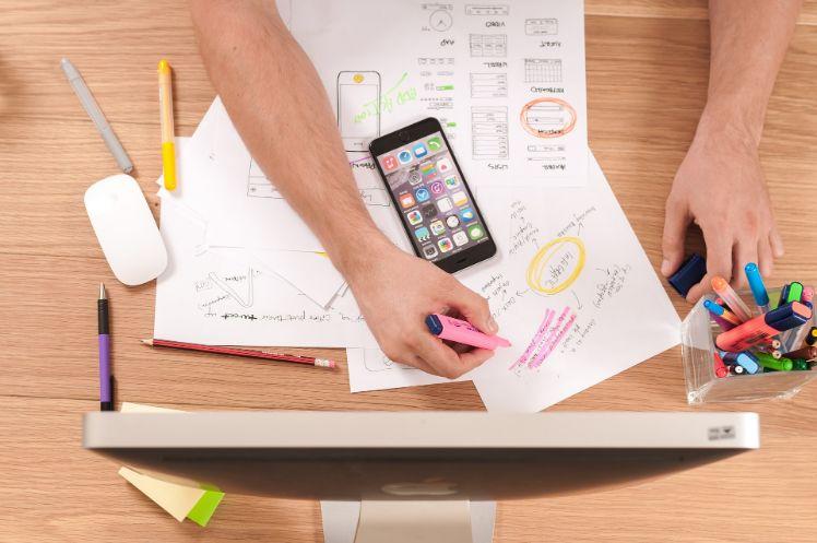 Mann erstellt Konzept auf Papier mit Stiften und iPhone und Bildschirm
