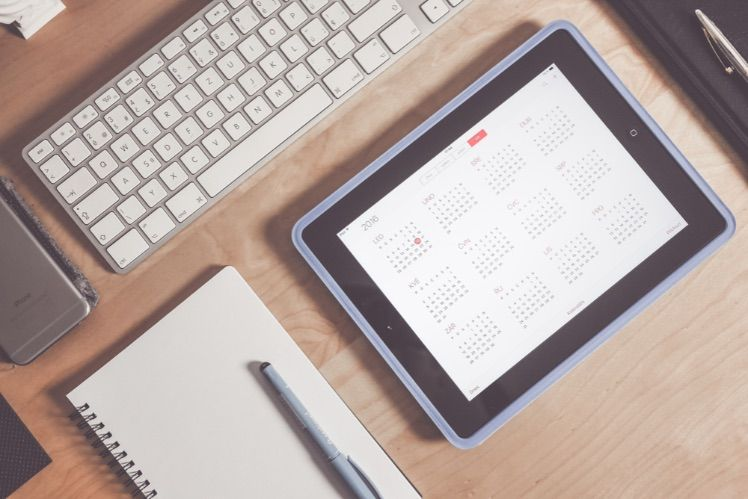 Stift auf Notizbuch liegt neben Kalender in iPad und Tastatur