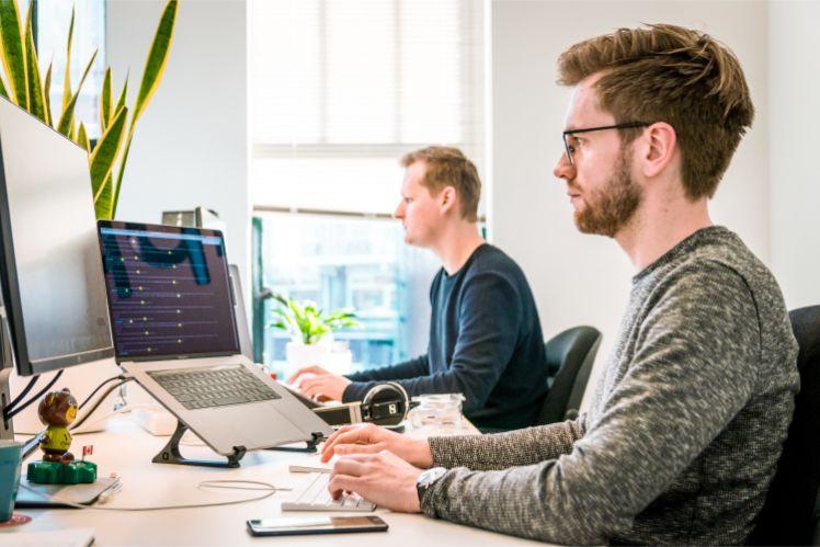Zwei Programmierer sitzen an ihren laptops und programmieren