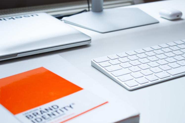 Buch mit brand identity liegt neben Tastatur laptop und Bildschirm