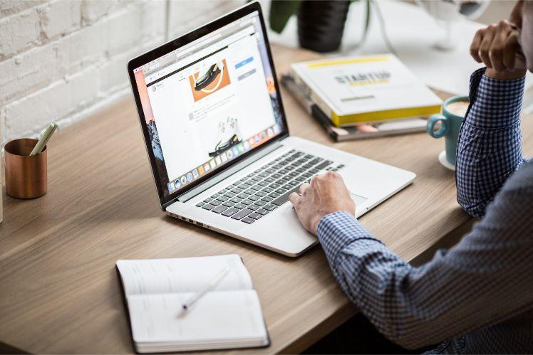 Mann sitzt an Schreibtisch und arbeitet an website