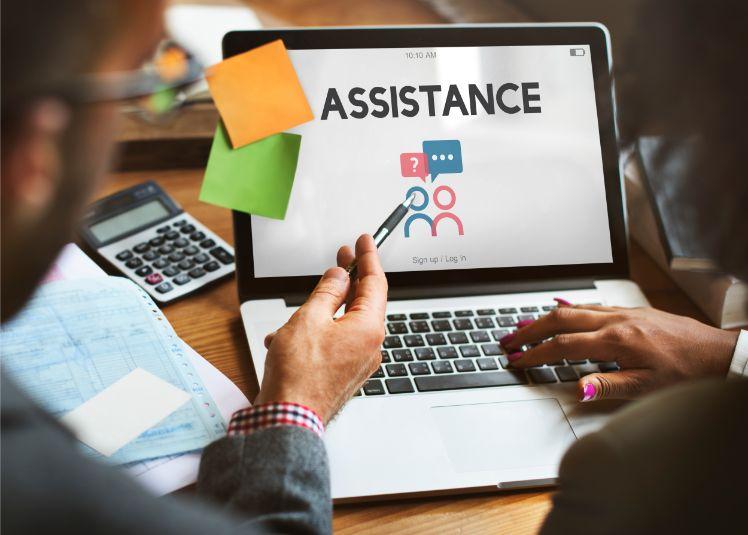 Mann zeigt Frau etwas auf laptop mit Aufschrift assistance