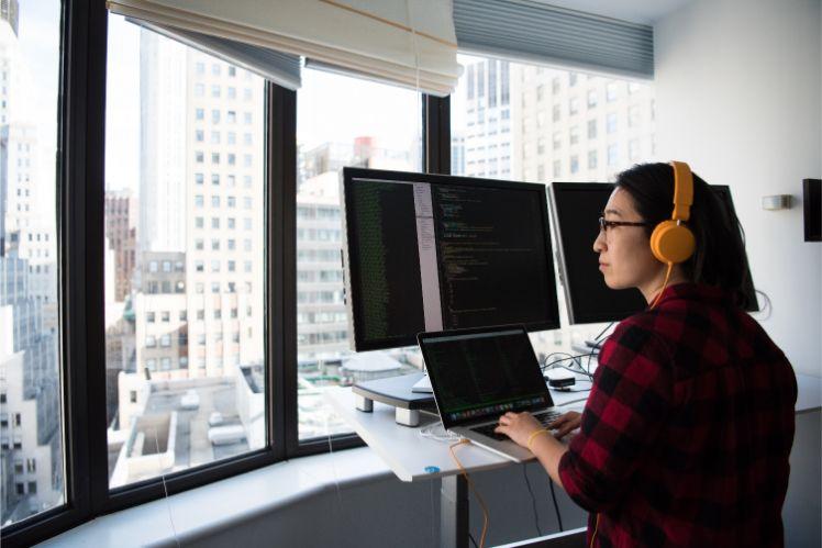 Frau mit orangenen Kopfhoerern steht vor laptop und desktops und programmiert
