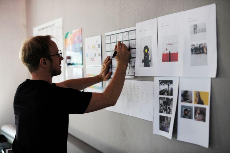 Mann steht vor Moodboard mit diversen bildern und schreibt auf ein blatt papier
