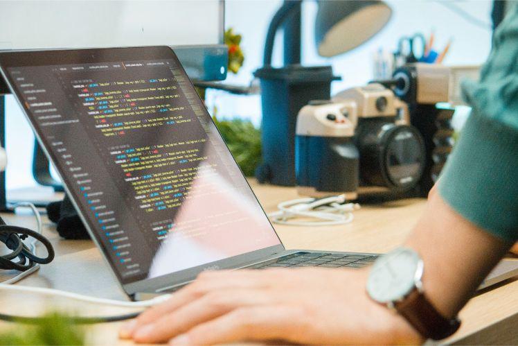 Mann mit Armbanduhr steht vor Laptop und programmiert