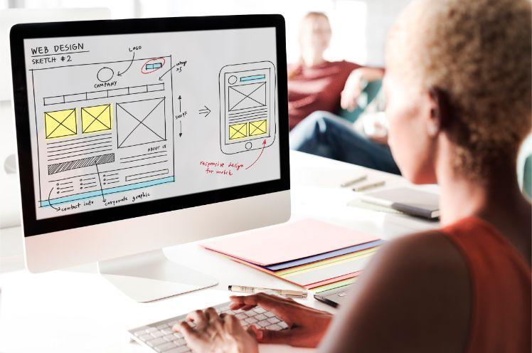 Frau sitzt an desktop und erstellt mockup fuer web design