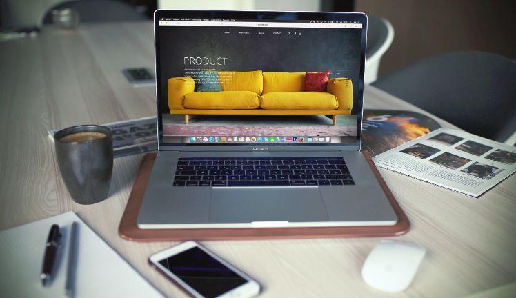 Laptop auf Schreibtisch mit anderen Medien im Hintergrund