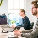 Programmierer sitzt vor seinem Laptop und schreibt code