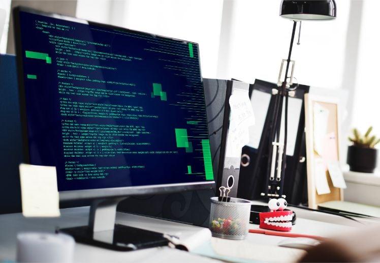 bildschirm auf Schreibtisch mit codiertem Text