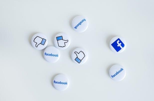 Weisse button pins mit blauer Schrift von facebook