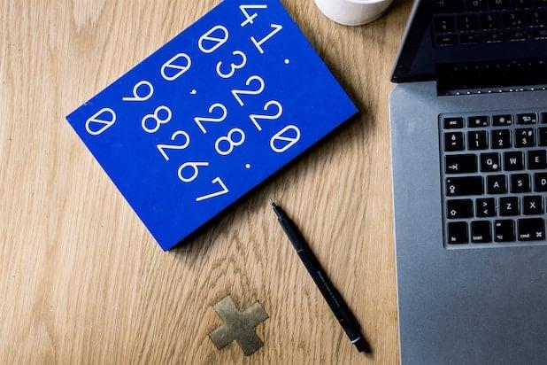 Blauer Notizblock mit Zahlen neben Laptop und Stift