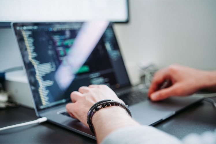 Mann arbeitet an Laptop mit Codes