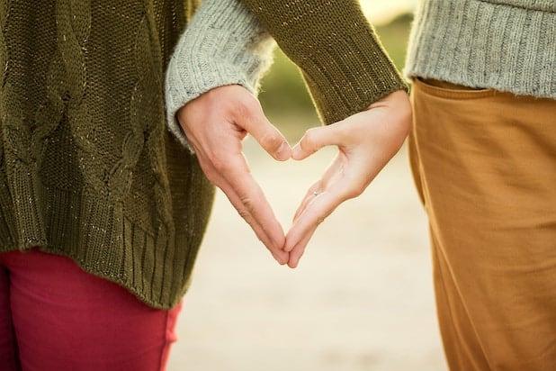 Zwei Menschen stehen nebeneinander und formen mit ihren Haenden ein Herz