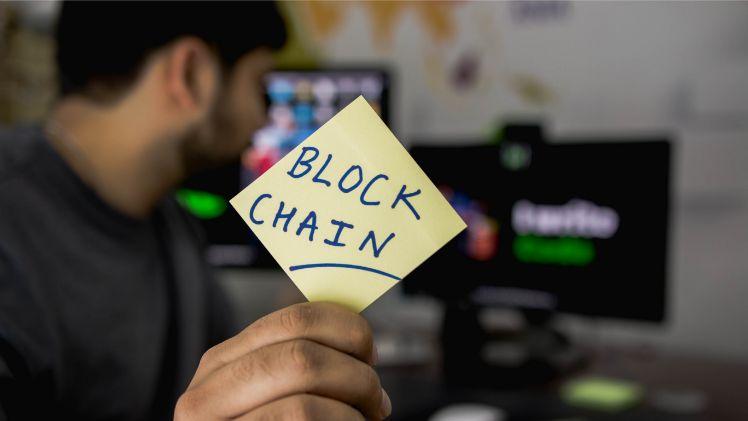 Mann haelt Post it in der Hand mit der Aufschrift Blockchain