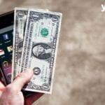 Hand haelt Smartphone und Geld