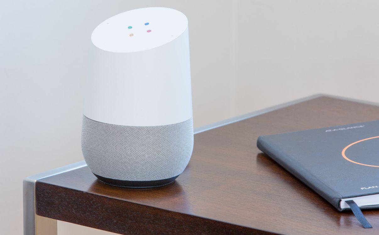 Google home geraet auf tisch neben notizbuch