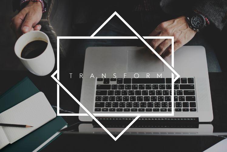 laptop neben kaffee und notizheft und grosse weisse aufschrift transform